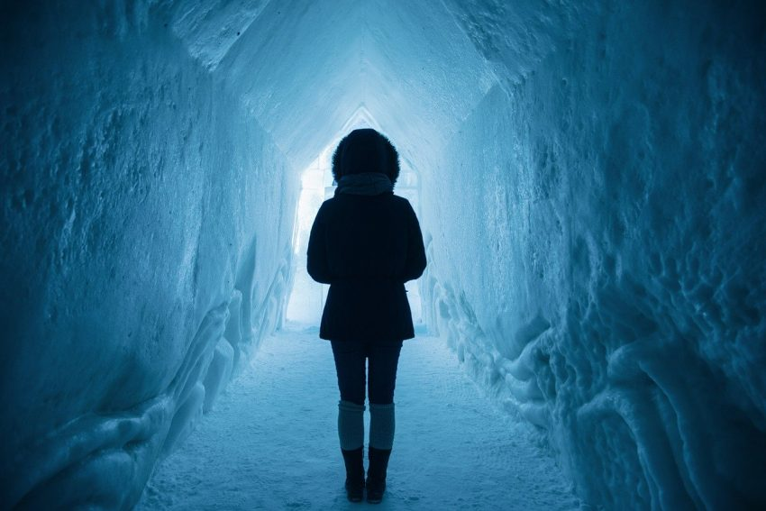 Woman in parka standing in an ice cave