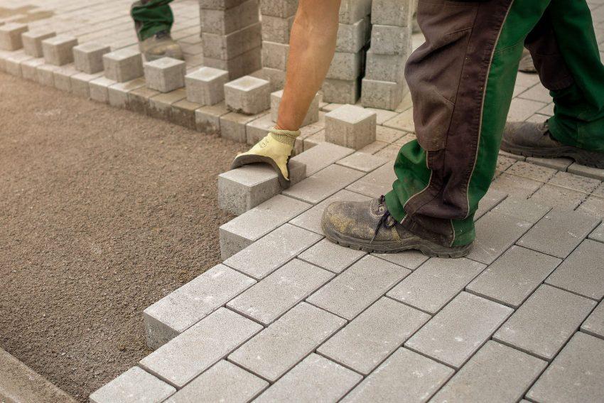Brick mason building a pathway